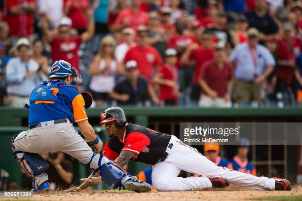 Edwin Jackson of the Washington Nationals is tagged out at home plate by Travis d'Arnaud of the New York Mets in the ninth inning during Game One of...