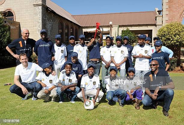Edwin Moses Laureus academy chairman and Franz Beckenbauer Laureus academy member pose with children from the Sport for all Laureus 'Sport for Good'...