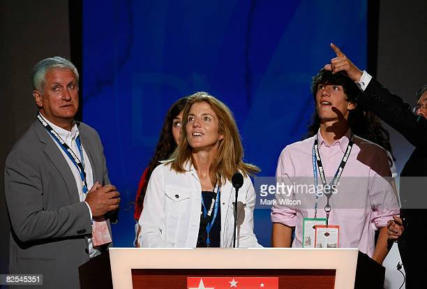 Edwin Schlossberg his wife Caroline Kennedy Schlossberg and son Jack Schlossberg stand at the podium before the first session of day one of the...
