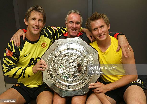 Edwin van der Sar Goalkeeping coach Eric Steele and Tomasz Kuszczak of Manchester United pose in the dressing room with the Community Shield after...
