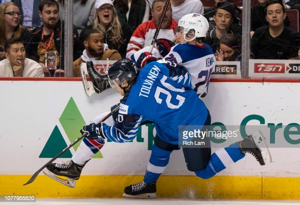 Eeli Tolvanen of Finland hits Phil Kemp of the United States along the side boards in Gold Medal hockey action of the 2019 IIHF World Junior...