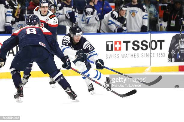 Eeli Tolvanen of Finland passes the puck with Martin Fehérváry of Slovakia closing in during the second period of play in the IIHF World Junior...