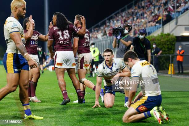 Eels players look on despondent as Moses Suli of the Sea Eagles celebrates after scoring a try during the round 22 NRL match between the Manly Sea...