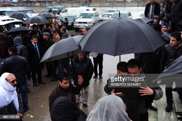 Eeraj the nephew of slain Afghan AFP reporter Sardar Ahmad is comforted by a friend during funeral ceremonies for Sardar and his family in Kabul on...