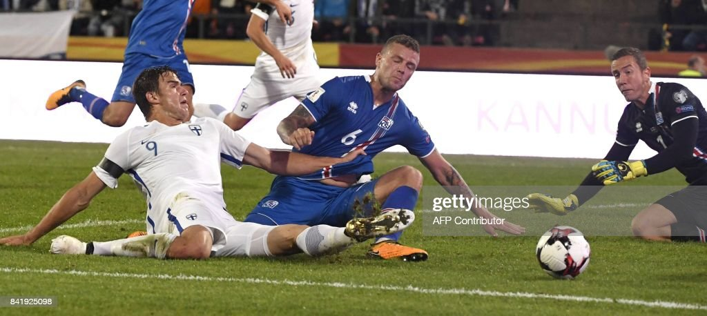 Eero Markkanen (L) of Finland vies with Ragnar Sigurdsson of Iceland in front of goalkeeper Hannes Halldorsson of Iceland during the FIFA World Cup 2018 qualification football match between Finland and Iceland in Tampere on September 2, 2017. / AFP PHOTO / Lehtikuva / Jussi Nukari
