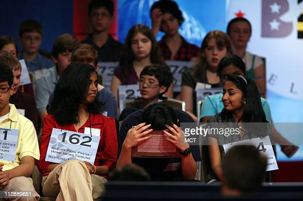 Eesha Anagha Ramanujam and Shyamala Ramakrishna watch as Michael Sun hangs his head as they wait their turns in the first live round at the National...