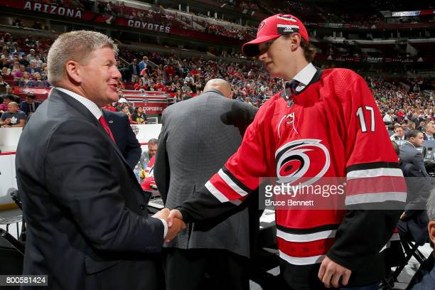 Eetu Luostarinen meets with coach Bill Peters after being selected 42nd overall by the Carolina Hurricanes during the 2017 NHL Draft at the United...
