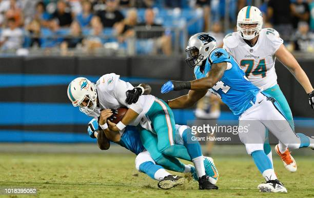 Efe Obada of the Carolina Panthers sacks Brock Osweiler of the Miami Dolphins in the second quarter during the game at Bank of America Stadium on...
