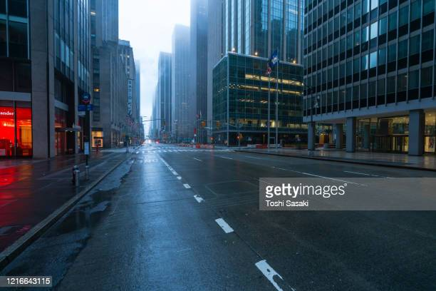 covid-19 effect to new york city. people and traffic disappeared from midtown manhattan 6th avenue for impact of covid-19 in the rainy morning new york city ny usa on mar. 29 2020. - empty city coronavirus stock pictures, royalty-free photos & images