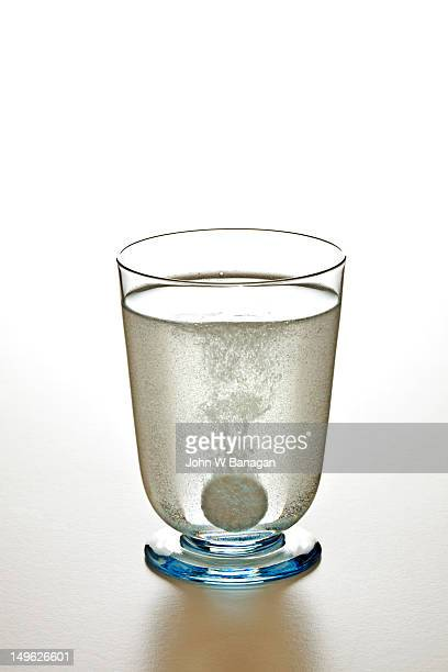 Effervescent pill dissolving in a glass of water