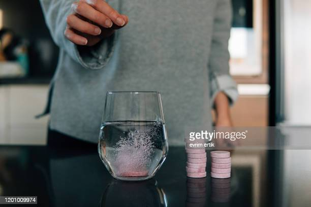 effervescent tablets in water on the table - vitamin c stock pictures, royalty-free photos & images