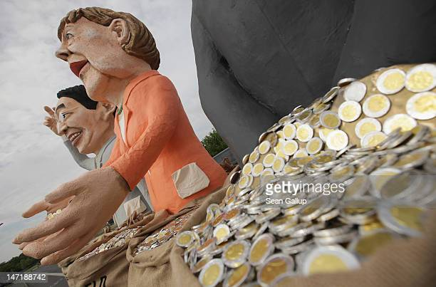 Effigies in the likeness of German Vice Chancellor and Economy Minister Philipp Roesler and German Chancellor Angela Merkel stand on a truck near the...