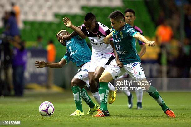 Efrain Velarde and Jonathan Gonzalez of Leon vies for the ball with Eisner Loboa of Atlas during their Mexican Apertura tournament football match at...