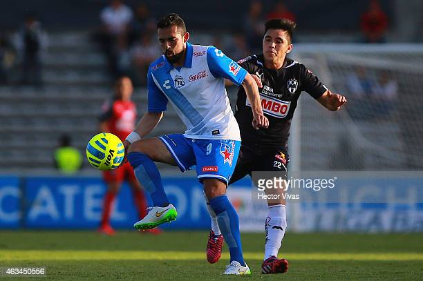 Efrain Velarde of Monterrey struggles for the ball with Herculez Gomez of Puebla during a match between Puebla and Monterrey as part of 6th round...