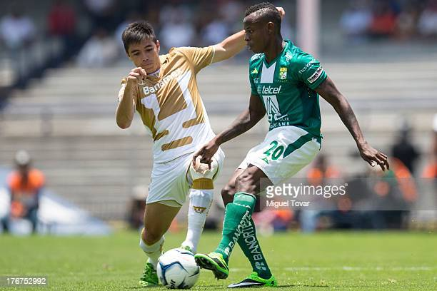 Efrain Velarde of Pumas fights for the ball with Eisner Loboa of Leon during a match between Pumas and Leon as part of the Apertura 2013 Liga MX at...