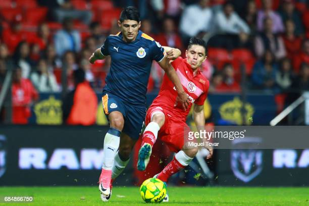 Efrain Velarde of Toluca fights for the ball with Alan Pulido of Chivas during the semifinals first leg match between Toluca and Chivas as part of...