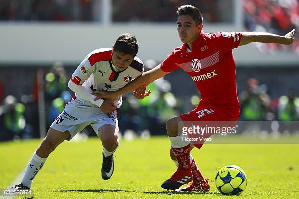 Efrain Velarde of Toluca struggles for the ball with Bryan Garnica of Atlas during the 1st round match between Toluca and Atlas as part of the Torneo...