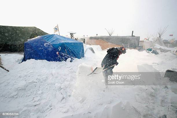 Efrem John a Dine Navajo from Shiprock New Mexico clears snow from his camp while winds whip across Oceti Sakowin Camp as blizzard conditions grip...