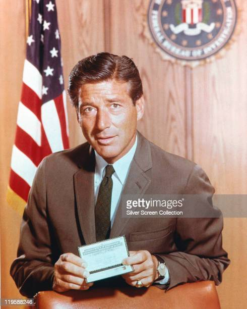 Efrem Zimbalist Jr US actor holding his identification card while on the wall behind him hang the flag of the United States and the seal of the FBI...