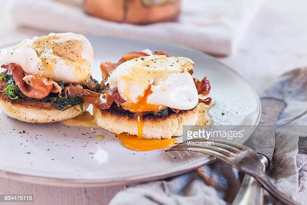 Egg Benedict with english muffins, poached eggs, ham, braised spinach, and Hollandaise