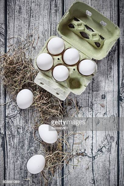 Egg carton with white eggs and hay on wooden boards, view from above