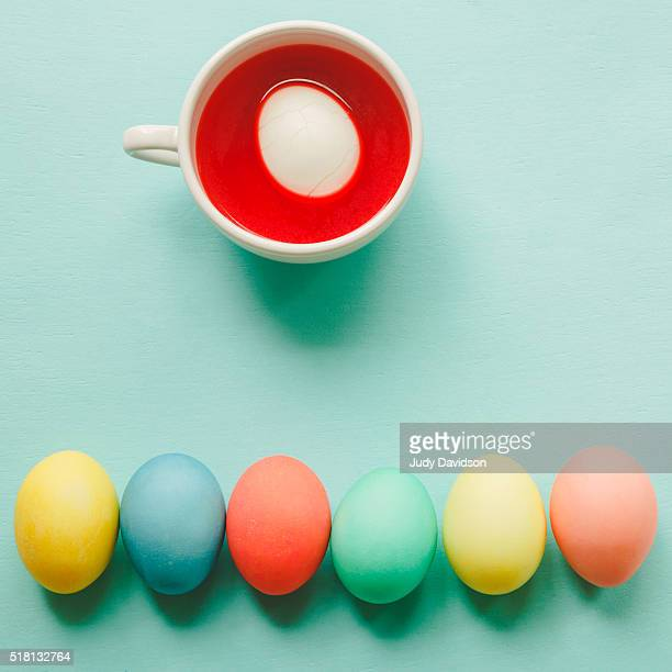 egg dying set up with a row of colored eggs and a cup full of egg dye - dye stock pictures, royalty-free photos & images