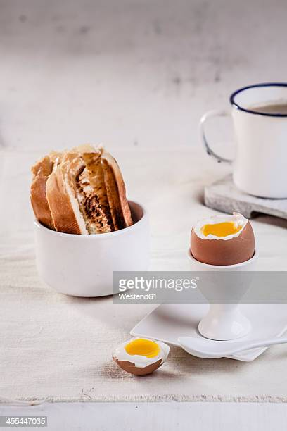 Egg in egg cup with toasted white bread and coffee mug, close up