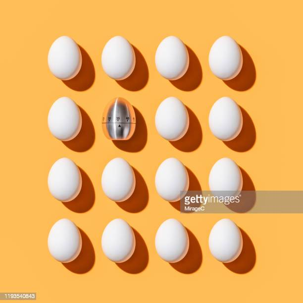 egg shaped timer among white eggs - individuality stock pictures, royalty-free photos & images