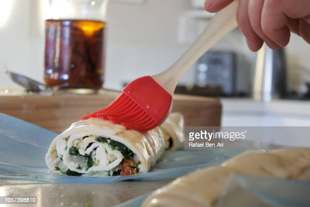 egg wash brushed onto spanakopita spinach pie greek savory pastry - rafael ben ari fotografías e imágenes de stock