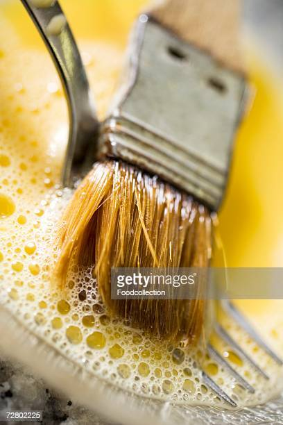 egg yolk with pastry brush and fork (close-up) - basting brush stock photos and pictures