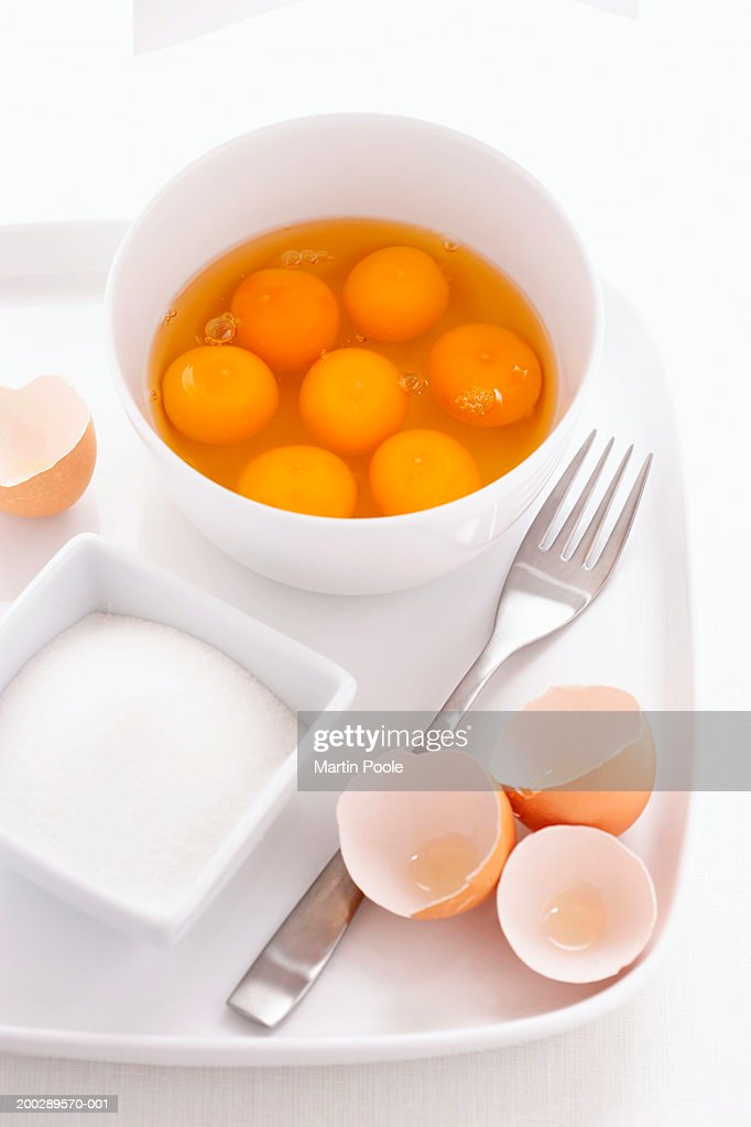 Egg yolks and egg whites in bowl, with eggshells, fork and sugar bowl on tray, close-up : Stock Photo