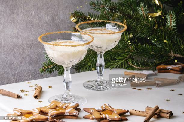 Eggnog Christmas milk cocktail served in two vintage crystal glasses with shortbread star shape sugar cookies cinnamon sticks fir branch over white...