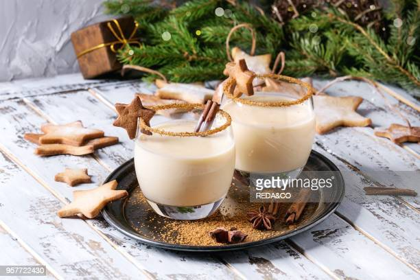Eggnog Christmas milk cocktail with cinnamon served in two glasses on vintage tray with shortbread star shape sugar cookies decor toys fir branch...