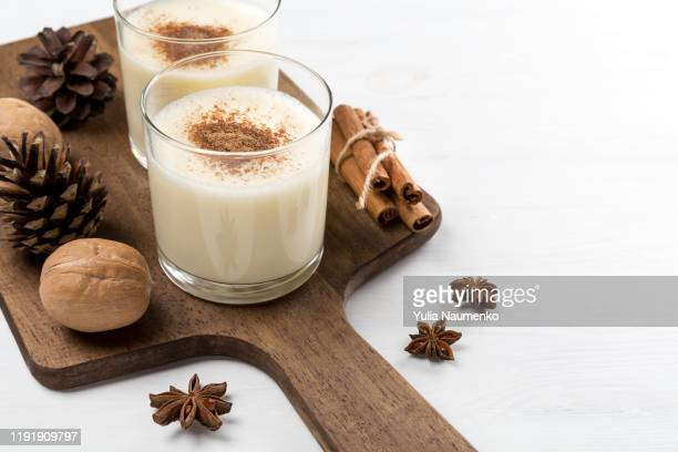 eggnog in glasses with star anise, cinnamon and walnuts and fir cones on a white wooden background. - liqueur stock pictures, royalty-free photos & images