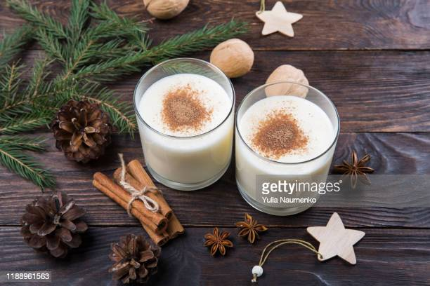 eggnog with cinnamon in glasses on wooden background, christmas decor, traditional festive drink. - eggnog stock photos and pictures