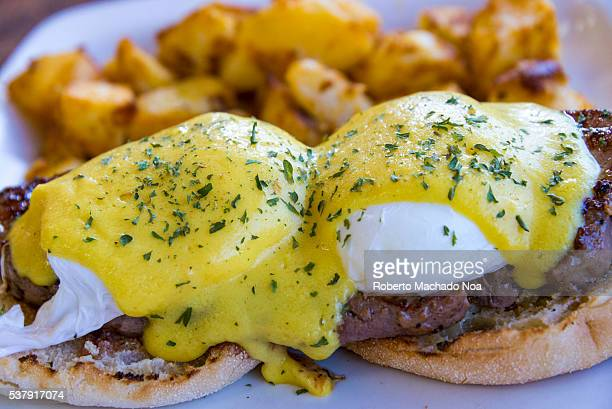 Eggs Benedict over a beef sirloin steak high protein breakfast plate The dish also includes English muffin toasts with English sausage with fried egg...