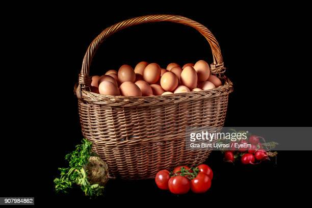 Eggs In Basket With Vegetables Over Black Background