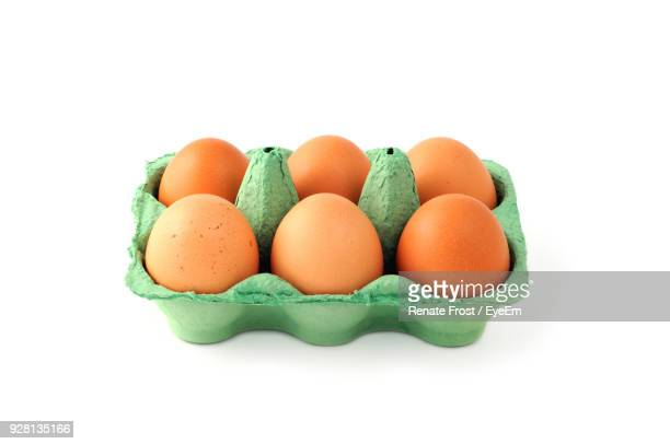 eggs in carton over white background - carton stock photos and pictures