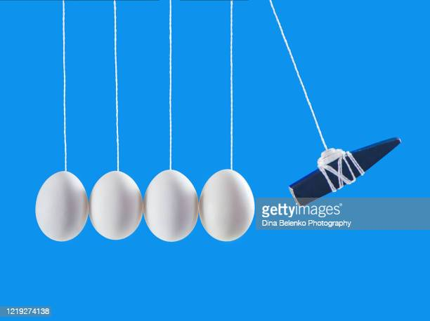 eggs in newton's cradle with a hammer, levitation food photography, minimalist creative scene - fragility stock pictures, royalty-free photos & images