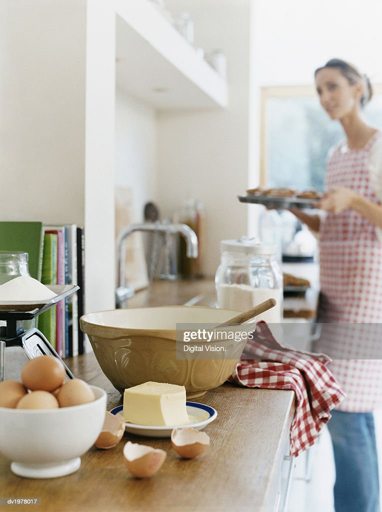 Eggs, Kitchen Scales, Butter and a Bowl With Spoon on Kitchen Counter, Woman Holding a Baking Tray on Background : Stock Photo