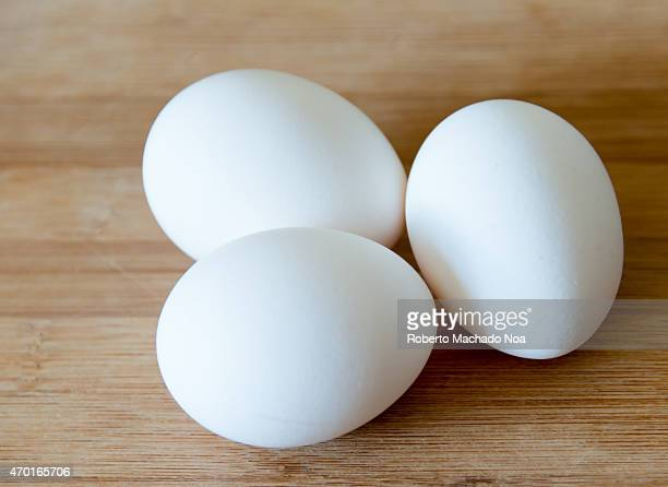 Eggs realistic approach to food ingredients Three white eggs over a wooden surface or cutting board in a kitchen some shallow depth of field and...