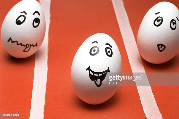 3 eggs with different expressions drawn in on a race field