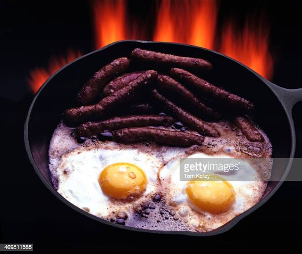 Eggs with sausage in cast iron pan with flames cooking cowboy style 2002