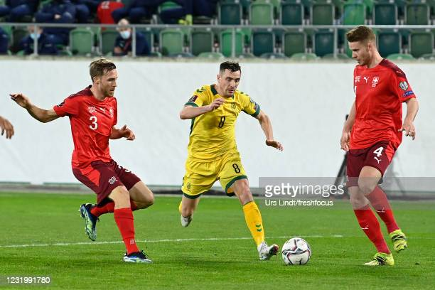 Egidijus Vaitkunas of Lithuania is challenged by Silvan Widmer of Switzerland Nico Elvedi of Switzerland during the FIFA World Cup 2022 Qatar...