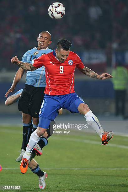 Egidio Arevalo of Uruguay goes for a header with Mauricio Pinilla of Chile during the 2015 Copa America Chile quarter final match between Chile and...