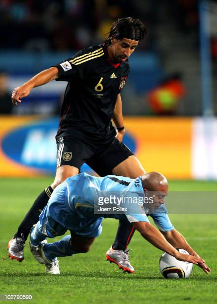 Egidio Arevalo of Uruguay is challenged by Sami Khedira of Germany during the 2010 FIFA World Cup South Africa Third Place Playoff match between...