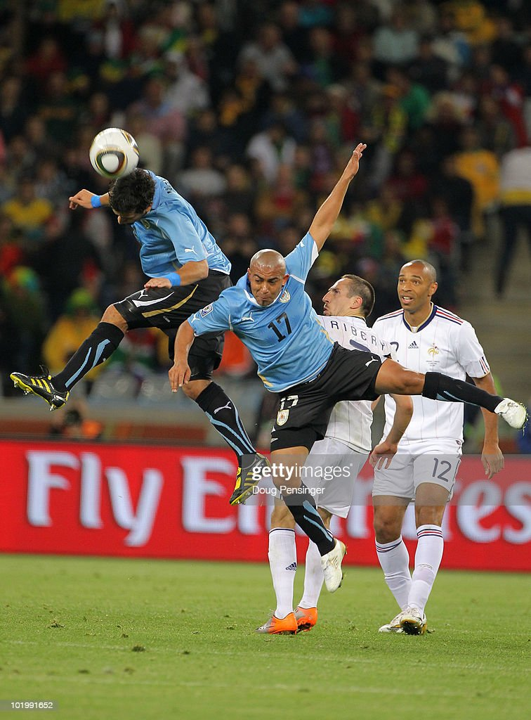 Egidio Arevalo Rios (C) and Mauricio Victorino of Uruguay both go in for a challenge on Franck Ribery of France during the 2010 FIFA World Cup South Africa Group A match between Uruguay and France at Green Point Stadium on June 11, 2010 in Cape Town, South Africa.
