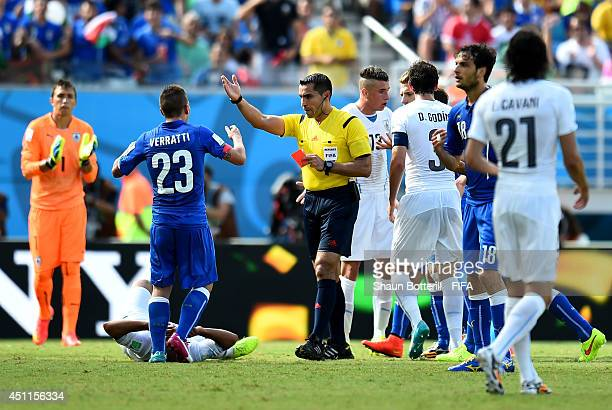 Egidio Arevalo Rios of Uruguay lies injured with referee Marco Rodriguez shows Claudio Marchisio of Italy a red card during the 2014 FIFA World Cup...