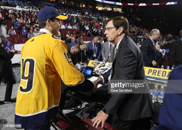 Egor Afanasyev, 45th overall pick of the Nashville Predators, is greeted at the draft table by general manager David Poile a the team draft table...