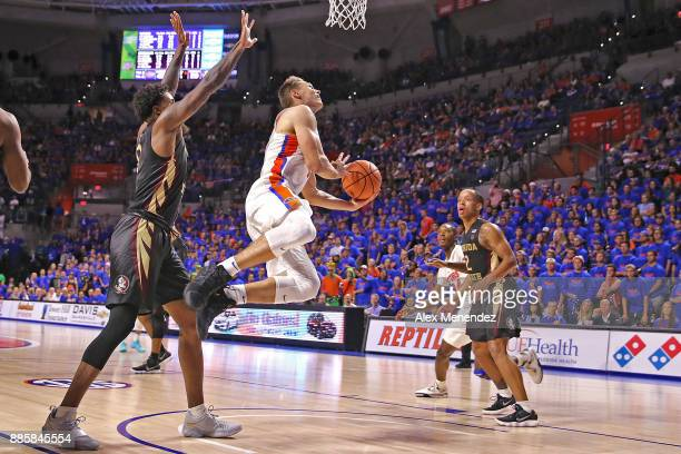 Egor Koulechov of the Florida Gators shoots the ball as he passes Phil Cofer of the Florida State Seminoles during a NCAA basketball game at the...